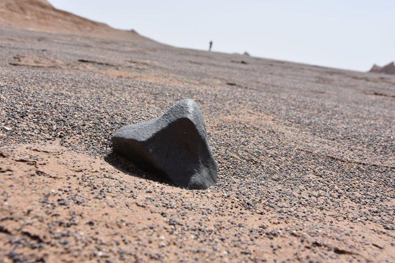 Uno degli esemplari più grandi rinvenuti: è una condrite di quasi un chilo  che presenta spaccature ed una bella crosta di fusione; sullo sfondo i Kalut